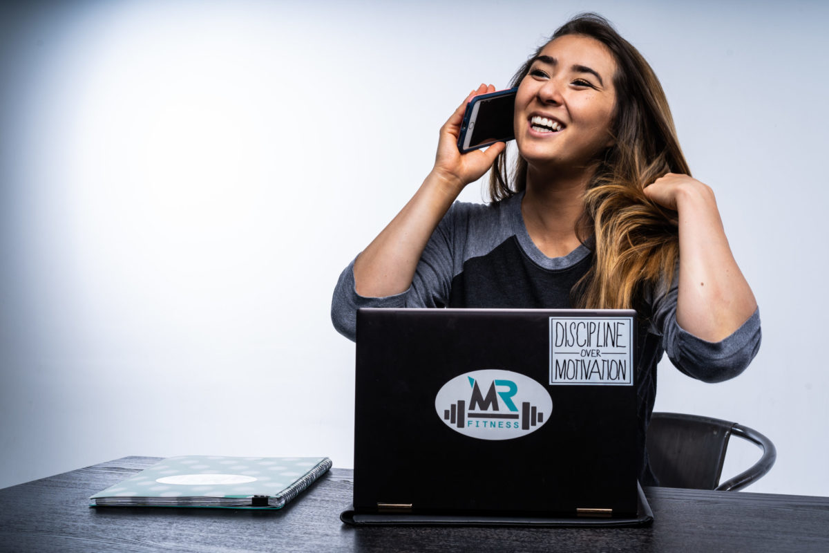 image of Marissa on her phone and laptop, smiling, talking to a client.